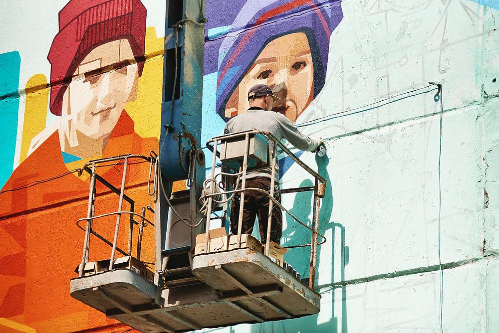 Рязанский уличный художник создал граффити с детьми 90-х в Тюмени