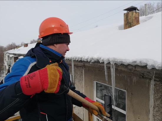 На фоне усиления уборки снега в Омске в центре города на краю крыши висит сугроб