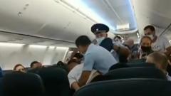 Полицейские вывели из самолета безмасочника: кадры дебоша