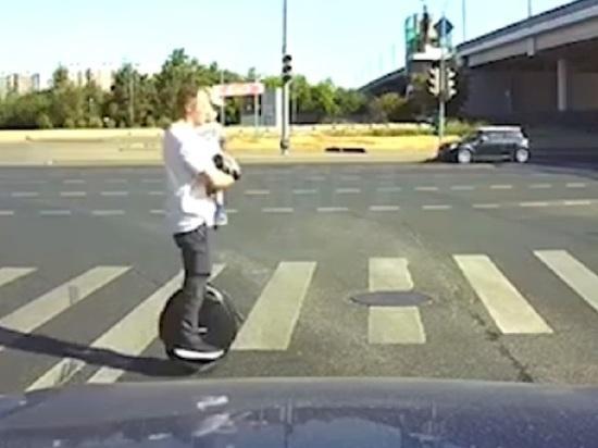 Отец на моноколесе промчался по дороге с ребенком на руках