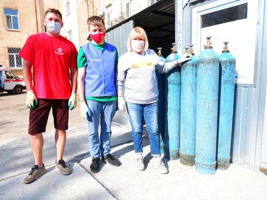 Волонтеры помогают работникам вологодского моногоспиталя выгружать кислородные баллоны