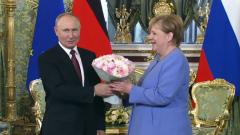 Путин подарил Меркель букет цветов и застенчиво улыбнулся: видео