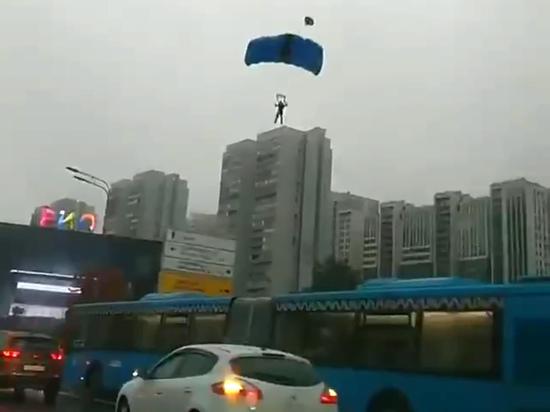 Автомобилисты, которые стояли утром в четверг, 23 сентября, в пробке на Ленинском проспекте, смогли насладиться необычным зрелищем: с высотного здания спрыгнули несколько парашютистов